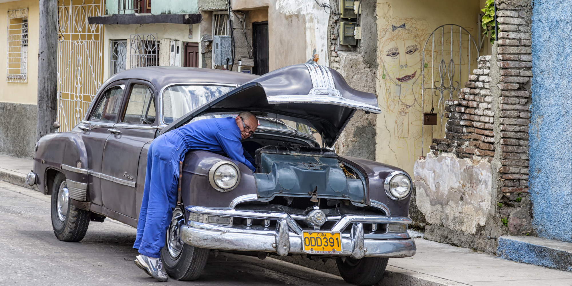 [UNVERIFIED CONTENT] Old American car being repaired by a mechanic on the side of the road in Holguin, Cuba.